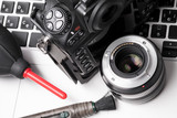 Digital camera, lens, cleaning tools on laptop. concept of photographer work station.