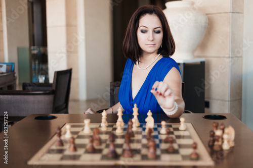 Fotografiet young beautiful woman playing chess