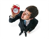 Deadline concept. Young stressed businessman is looking at clock. Isolated on white background.