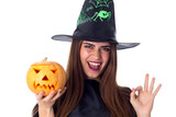 Woman in costume of witch holding a pumpkin and showing OKAY