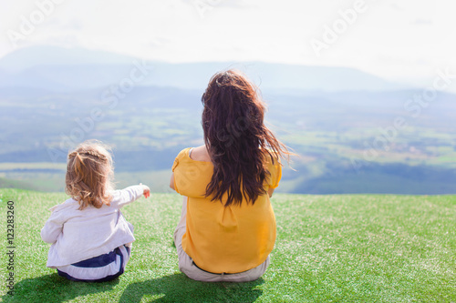 Poster Mother and daughter sitting on a meadow with a view