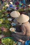 Vietnamese woman with typical conical hat , eating noodles in a street market