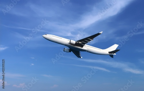Passenger airplane flying under cloudy blue sky