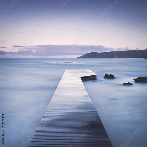 Fototapeta Wooden pier, rocks and sea on misty sunset.