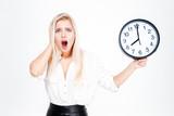 Surprised blonde businesswoman holding clock