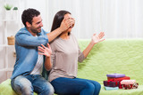 Young couple is sitting at sofa at home. Woman is surprised by many gifts.