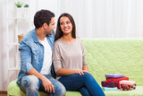 Young couple is sitting at sofa with present that they purchased.