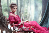 Portrait of a beautiful woman in a burgundy vintage dress sitting with a candle in her hand in the mysterious forest
