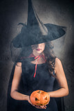 Halloween Witch with a magic Pumpkin. Beautiful young woman in witches hat and costume holding carved Jack lantern pumpkin