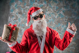 portrait of Santa Claus, a young man dressed in a stimpack hipster style he holding a new year