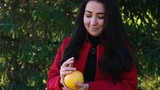 Girl in red coat is holding an orange
