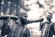 Two friends Lumberjack carrying wooden trunk.