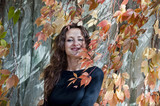pretty smiling woman in autumn leaves