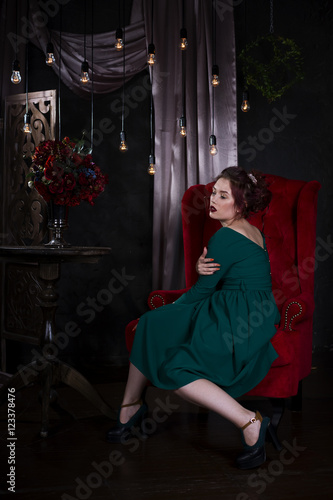 Young beautiful red-haired caucasian woman with professional makeup in green dress posing on red sofa © staras