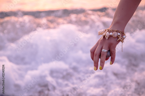 Woman holding stone near sea at sunset