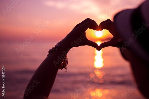 Billede Woman making heart of hands near sea at sunset