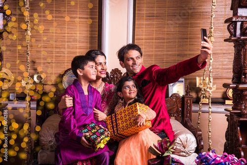 Asian Indian family taking selfie or self photograph at home with gift boxes on diwali festival