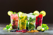 Different types of mojito cocktail on dark brown background