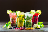 Fototapety Different types of mojito cocktail on dark brown background