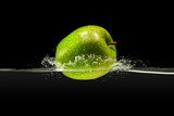 Green apple falling in water on black background