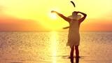 Happy woman enjoying a beautiful sunrise and sunset on the sea. Seascape during Sunrise. Beautiful Sunny Reflection on the Sea. Slow motion 240 fps.