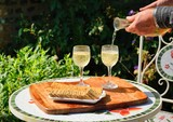 White wine being poured into galsses on garden table.
