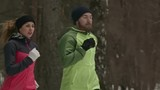 MS Tracking shot of sporty young man and woman practicing winter jogging in woodland