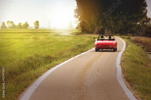 Plakat Classic red convertible car traveling in the countryside at sunset