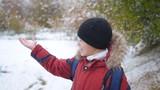 boy catches snowflakes