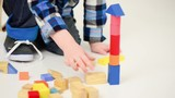 boy playing with colorful wooden blocks on white background