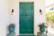 Green entry door with door knock.