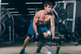 sport, fitness, lifestyle and people concept - flexing muscles with dumbbells in gym