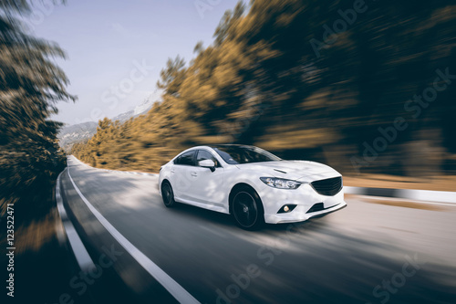 Fototapeta White car speed driving on asphalt road at daytime
