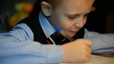 Boy 7 years of European appearance in school uniform adopted in Russia does his homework at his desk