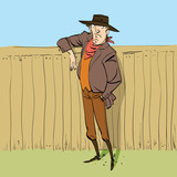 Cowboy in full figure standing near a fence