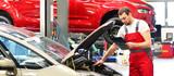 Kundendienst in einer Autowerkstatt - Mechaniker kontrolliert Fahrzeug - 123546660