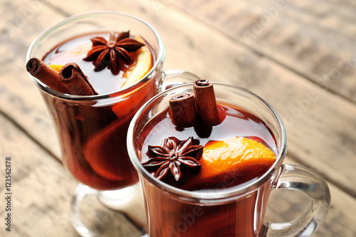 Glass cups of delicious Christmas mulled wine on wooden background, closeup