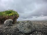 Grassy bluff among barren black rock wasteland