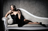 Film noir style: gorgeous beautiful young woman lying on sofa and smoking cigarette