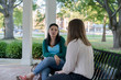 College aged female friends sitting and talking under a gazebo in a park