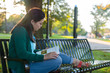 College aged girl sitting on a bench in a park reading a book