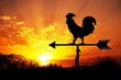 Rooster weathervane against sunrise with bright colors in clouds, concept for early morning wake up