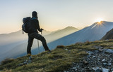 Fototapety Hiker with trekking poles and backpack.