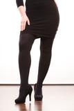 Female legs in black pantyhose heeled shoes