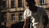 An African man dribbles a basketball.