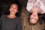two young girls playing on the floor with hair spread out