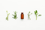 Bottle of essential oil with  fresh herbal sage, rosemary, lemon - 123603218
