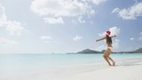 Christmas beach girl in santa hat jumping running having fun joyful and cheerful. Funny woman on Christmas vacation holidays travel getaway on white sand Caribbean beach. RED EPIC SLOW MOTION.