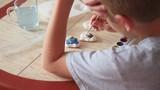 child paints the colors of plaster figures closeup