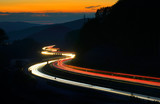 Winding Motorway through Hill Landscape at night, long exposure of headlights and taillights in blurred motion